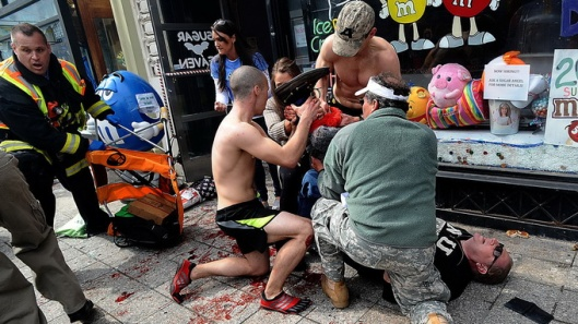 Bystanders tend to an injured man following explosions at the Boston Marathon finish area